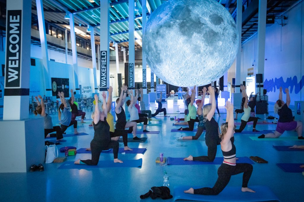 People do Yoga under a projection of the moon