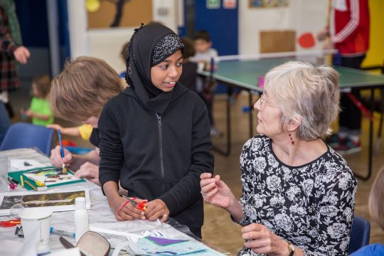 Older woman doing crafts with a young girl