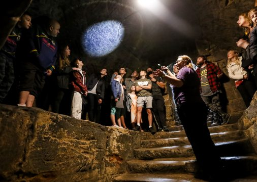 People look at torch on the ceiling of a dungeon