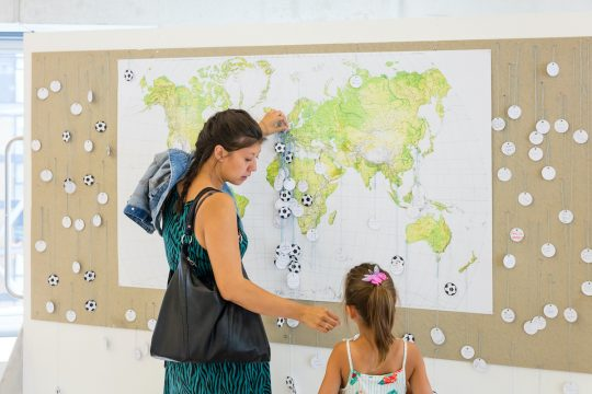 Woman pins a football to a world map