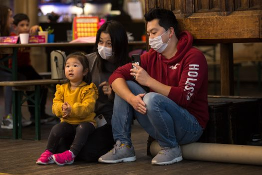 Family wearing masks watch an activity