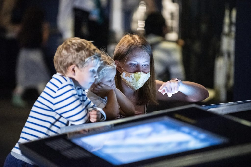 Young boy and woman looking at lit up display in a musuem