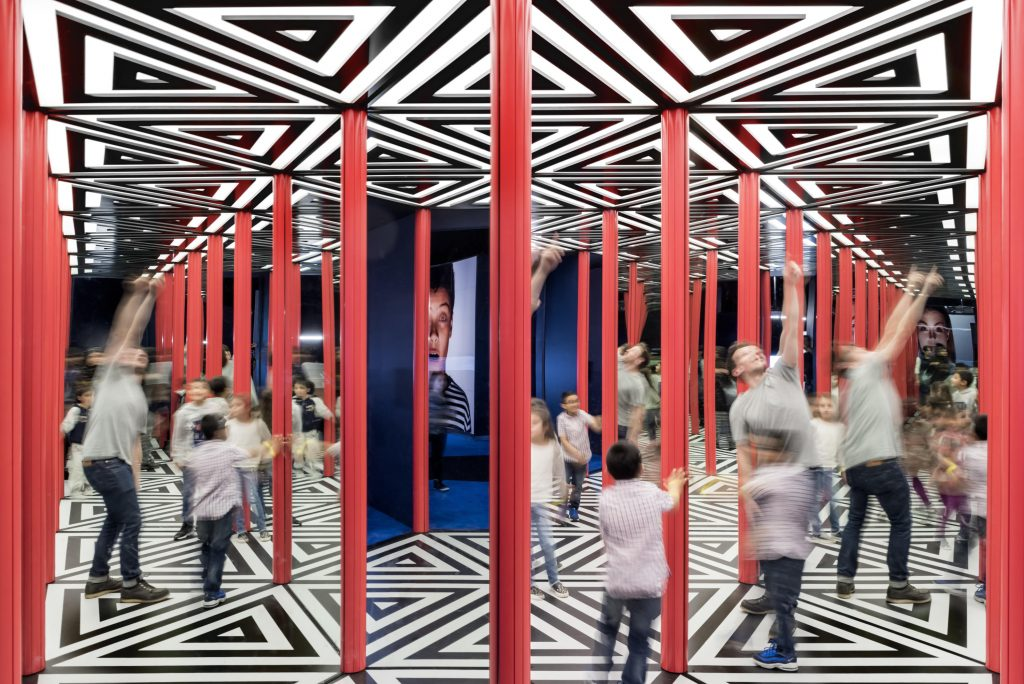 Children jumping in mirrored geometric space
