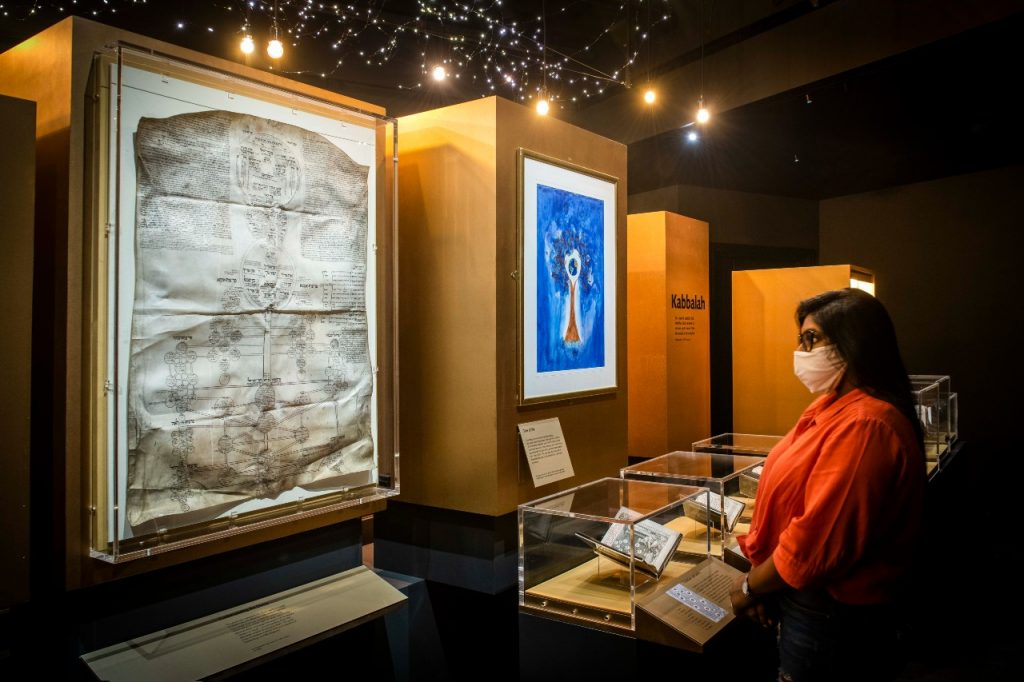 Person wearing mask looks at Hebrew manuscript exhibits