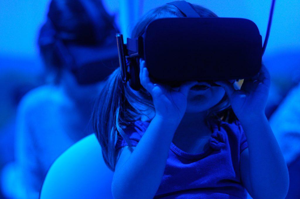 Child wearing virtual reality headset looking upwards.