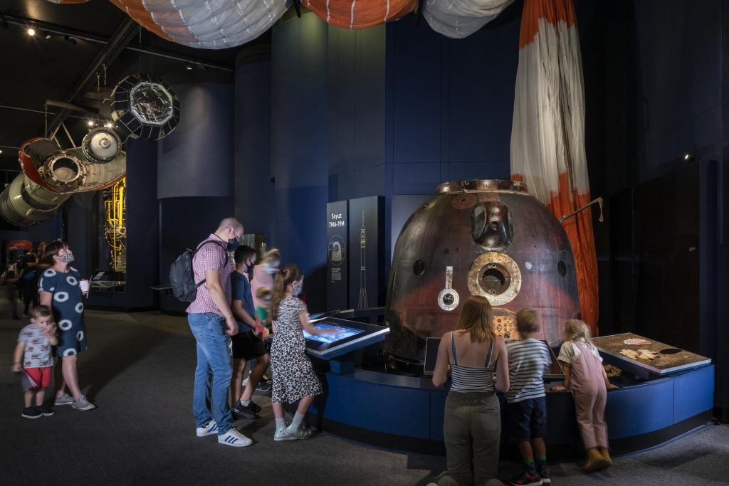 People in a museum looking at a space capsule