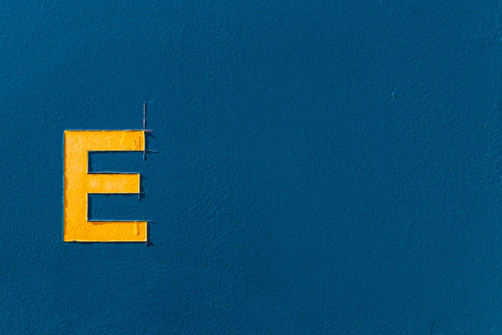 Captial letter 'E' in yelllow on a blue background