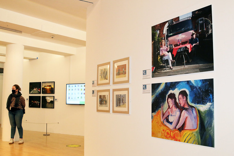 Image shows the inside of a gallery with white walls and images on the walls. In the background is a visitor wearing a face covering.