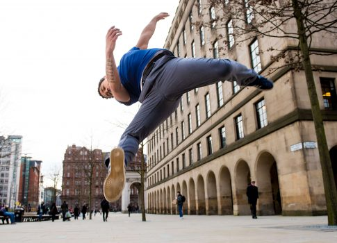 Photo of dancer jumping in the street with buildings in background